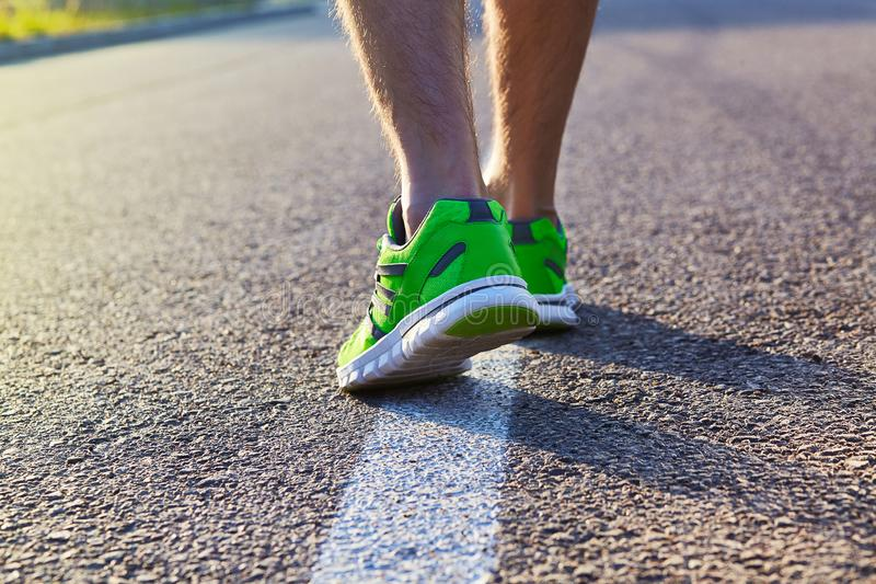 Runner man feet running on road closeup on shoe. Male fitness athlete jogger workout in wellness concept. Male athletes in running shoes. Jogging stock image