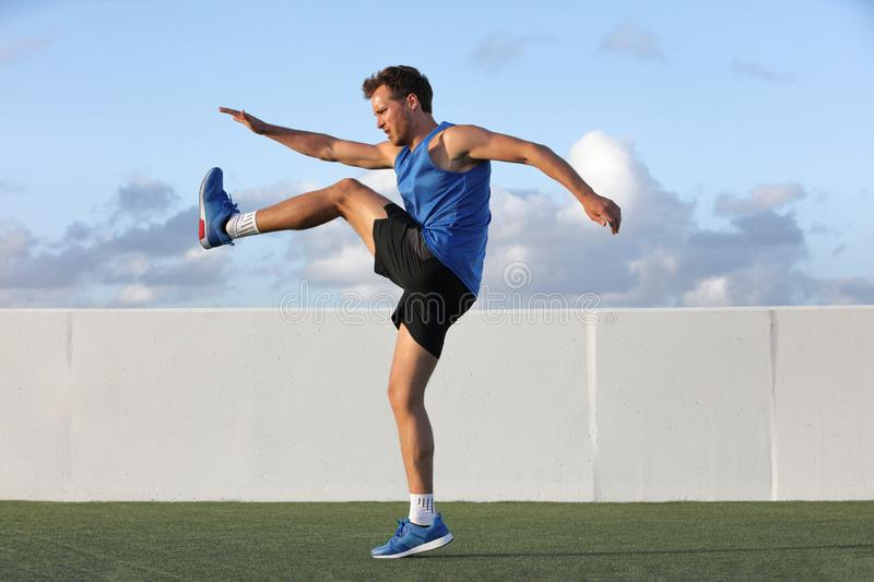 Runner man getting ready to run doing warm-up dynamic leg stretch exercises routine, Male athlete stretching lower body hamstring. Muscles before going running stock photo