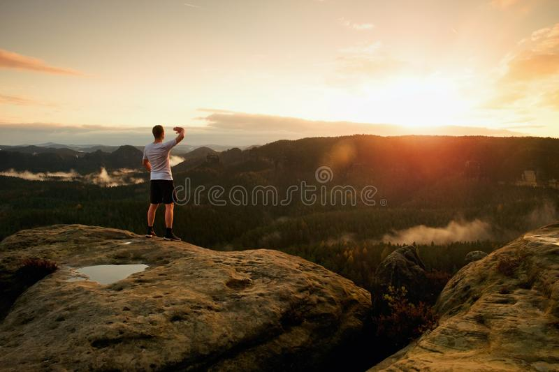 Runner man in his target with hand in the air. Sweaty man in black pants and white sweaty t-shirt,. Runner on the peak. Man in his target gesture triumph with stock photo