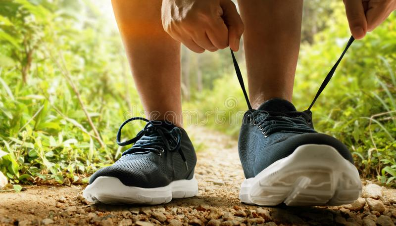 Runner man tying running shoes. Runner man tying running shoe royalty free stock photography