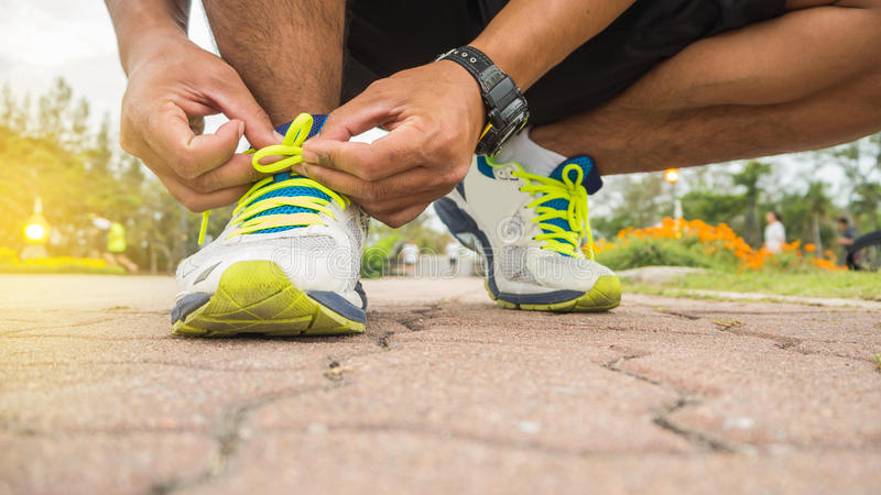 Runner man tying running shoes laces getting ready for race. On road royalty free stock images