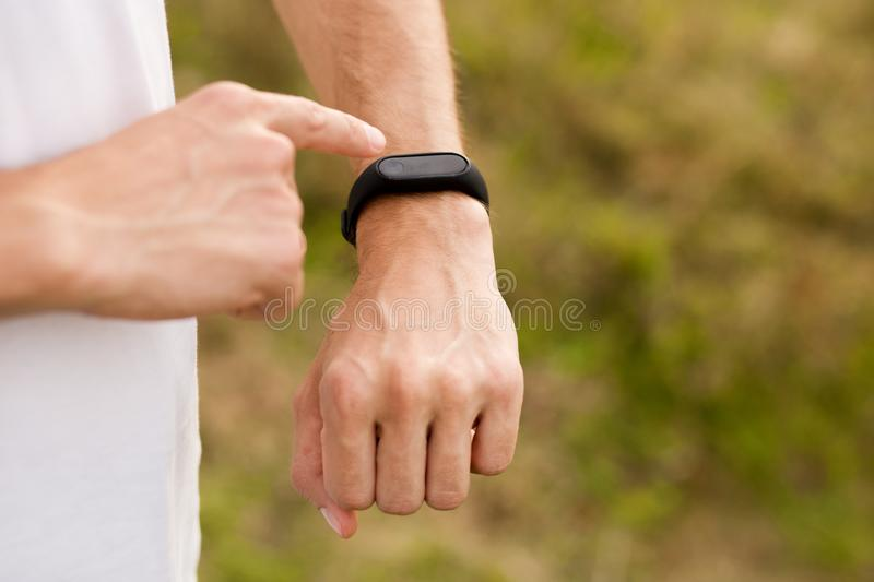 Runner on mountain trail looking at sports smart watch, checking performance or heart rate pulse trace. royalty free stock photo