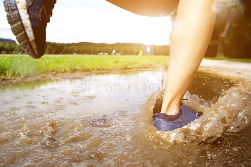 Runner& x27; piedi di s nella pozza di fango immagini stock libere da diritti