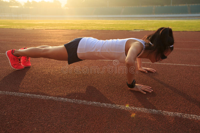 Runner push up on stadium track. Young fitness woman runner push up on stadium track stock images