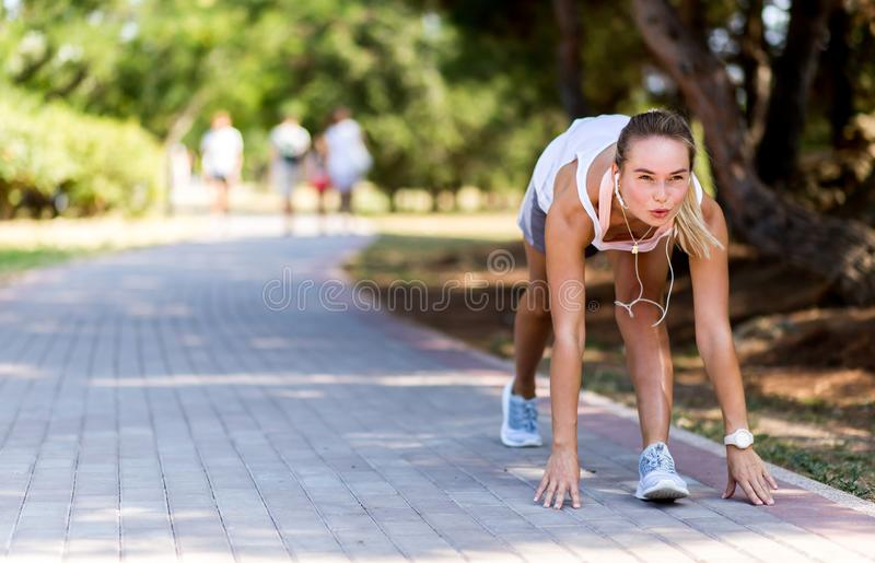 Runner woman jogging in summer fitness workout. Running, sport, healthy active lifestyle concept. At start. stock photo
