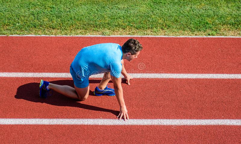 Runner ready to go. Athlete runner prepare to race at stadium. How to start running. Running tips for beginners. Man. Athlete stand low start position at stock photos