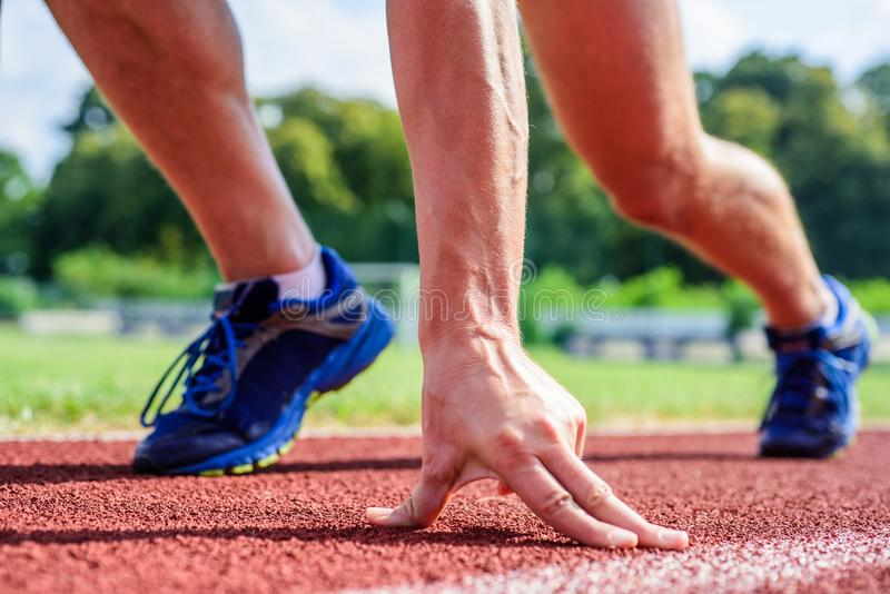 Runner ready to go close up. Ready steady go concept. At beginning of great sport career. Hand touch track path close up. Hand of sportsman on running track royalty free stock image