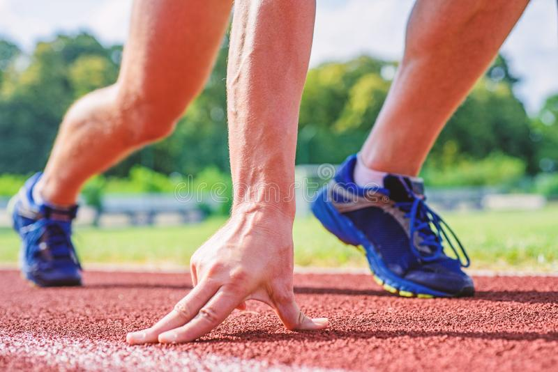 Runner ready to go close up. Ready steady go concept. At beginning of great sport career. Hand touch track path close up. Hand of sportsman on running track royalty free stock photography