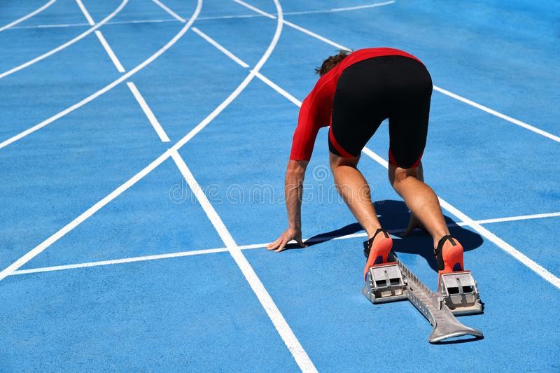 Runner ready to run on running track start line. Sport athlete going sprinting towards success on blue tracks. Sprinter on royalty free stock image