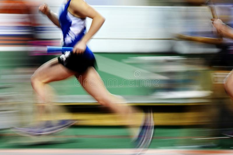 Runner Running a Race on Track with Baton Relay Team Score. Runner running a race on track with baton relay for team score competition royalty free stock photo