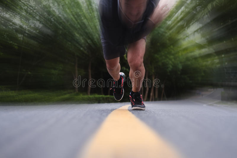 Runner running on the road, selective focus on shoes, with speed motion stock photography