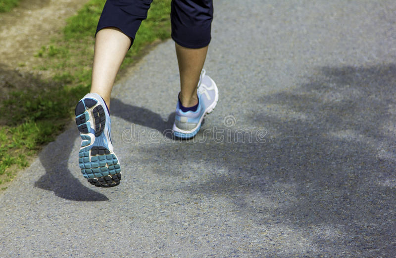 Runner - running shoes closeup on runners shoes feet running on road fitness jog workout healthy lifestyle fitness jogging. Concept royalty free stock photography
