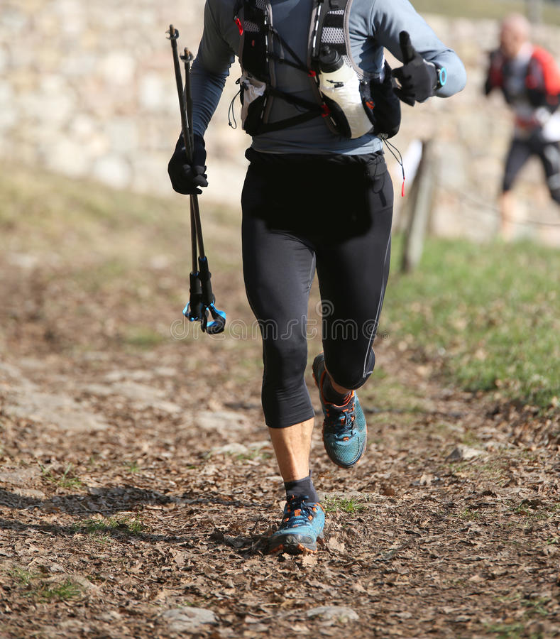 Runner runs in the mountains with nordic walking sticks. During a race stock photos