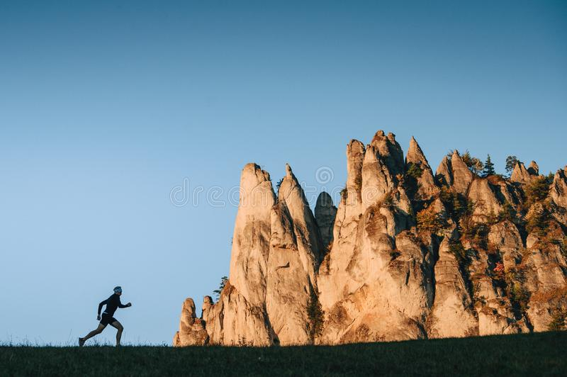 Runner silhouette and majestic rocks in background. Active life stock image