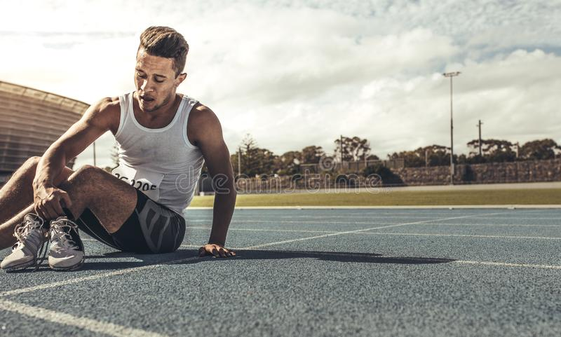 Runner sitting on running track holding his shoes. Athlete taking off his sprinting shoes after the race sitting on the track. Tired athlete relaxing on field stock photos
