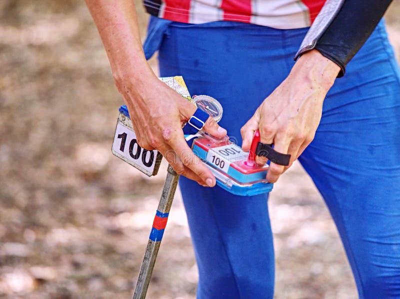 Runner skyndar sig att kontrollera sin position med ett finger arkivbild