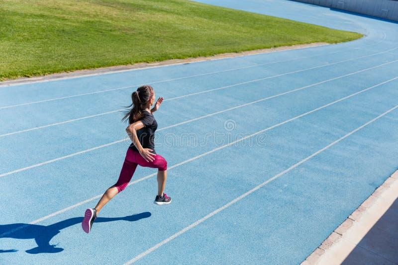 Runner sprinting towards success on running track stock photos