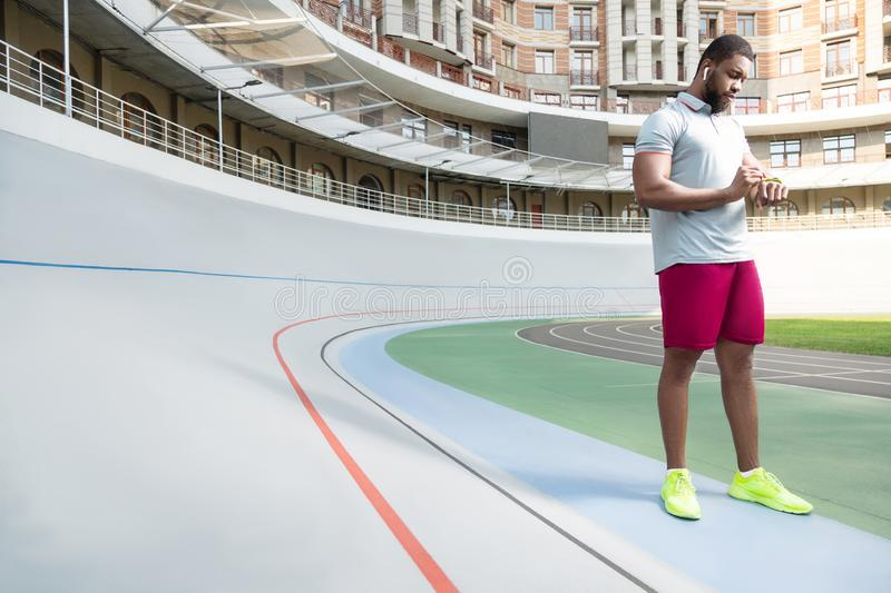 Runner standing in front of a high-rise building royalty free stock image