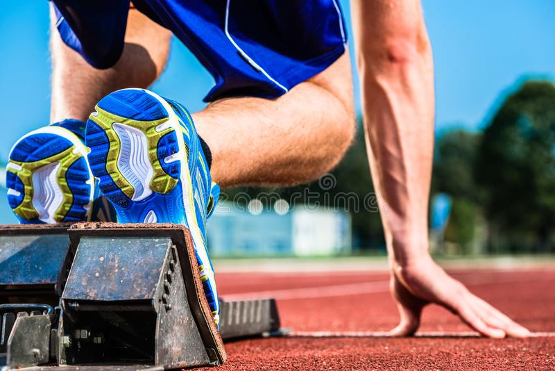 Runner before start signal on starting block of sprint track. In sport stadium stock image