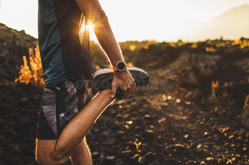 Runner stretching leg and preparing for running. Male runner stretching leg and feet and preparing for running outdoors. Smartwatches or fitness tracker on hand royalty free stock image