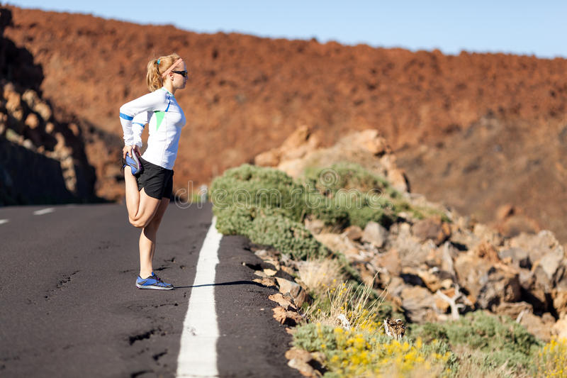 Runner stretching on road royalty free stock photos