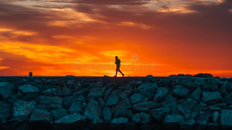 Runner at sunrise with the sun creating the silhouette stock image
