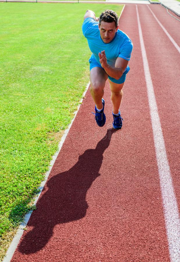 Runner take part competition motion forward. Focused on sport goal. Ready to achieve victory. Man athlete focused on stock photography