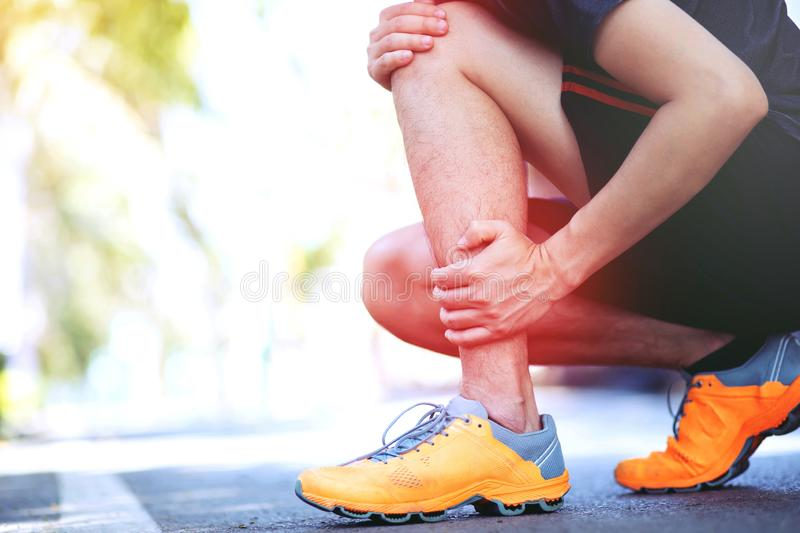 Runner touching painful twisted or broken ankle. Athlete runner training accident. Sport running ankle sprained sprain cause injur royalty free stock photo