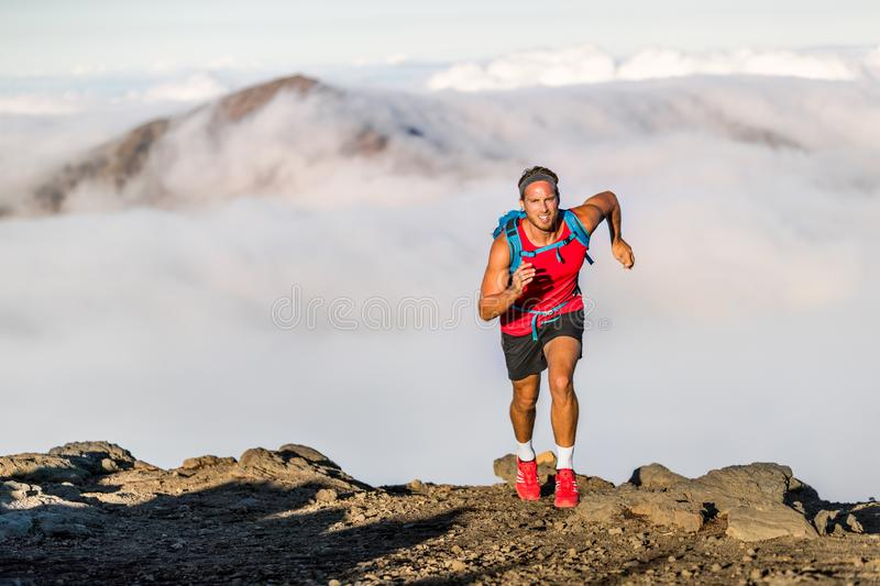 Runner trail running fitness man on endurance run - motivation and concentration on race in sky and clouds background on nature. Landscape. Focused athlete with royalty free stock images