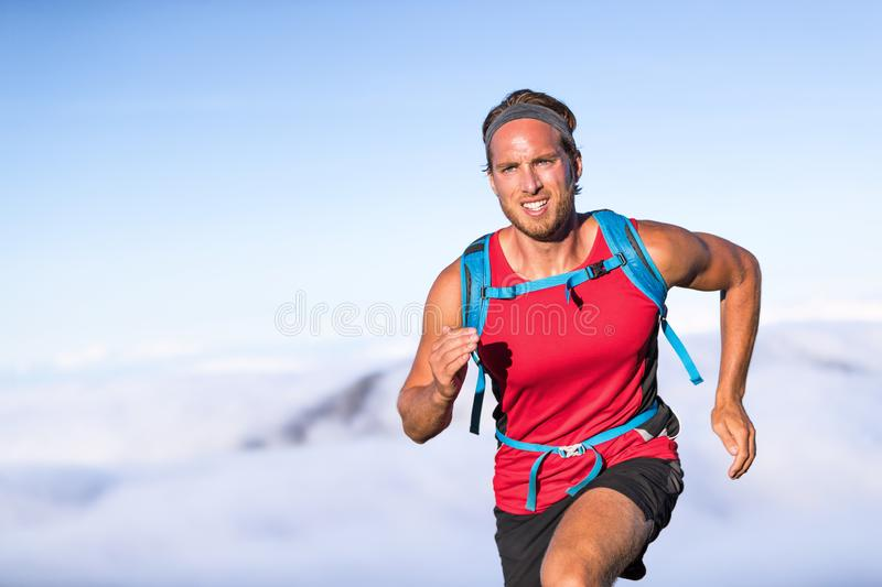 Runner trail running fitness man on endurance run - motivation and concentration on race in sky and clouds background on nature. Landscape. Focused athlete with royalty free stock image