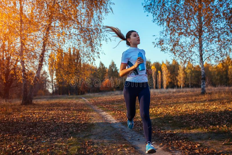 Runner training in autumn park. Woman running with water bottle and keeping fit at sunset. Active lifestyle royalty free stock photography