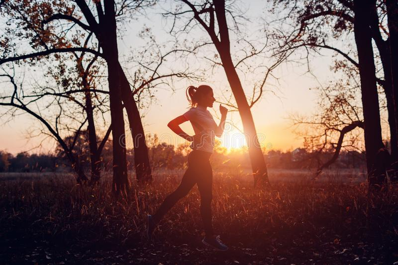 Runner training in autumn park. Woman running with water bottle at sunset. Active lifestyle royalty free stock photo