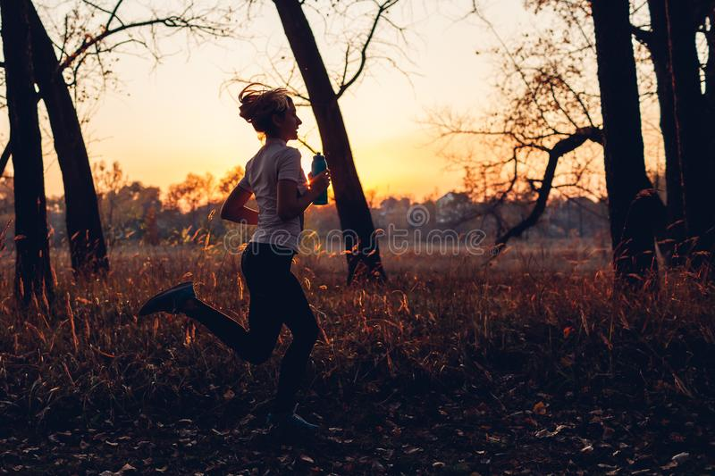 Runner training in autumn park. Woman running with water bottle at sunset. Active lifestyle. Silhouette royalty free stock photo