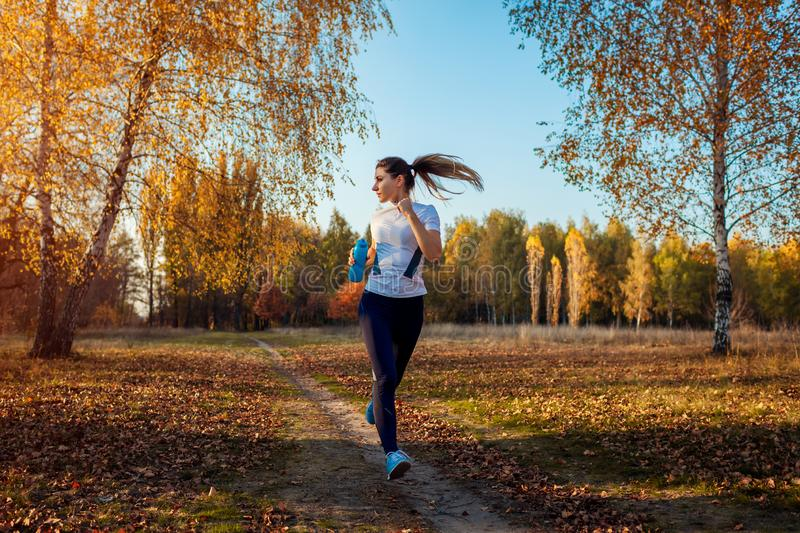 Runner training in autumn park. Woman running with water bottle at sunset. Active lifestyle stock photo