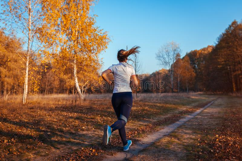 Runner training and exercising in autumn park. Woman running at sunset. Active healthy lifestyle royalty free stock images