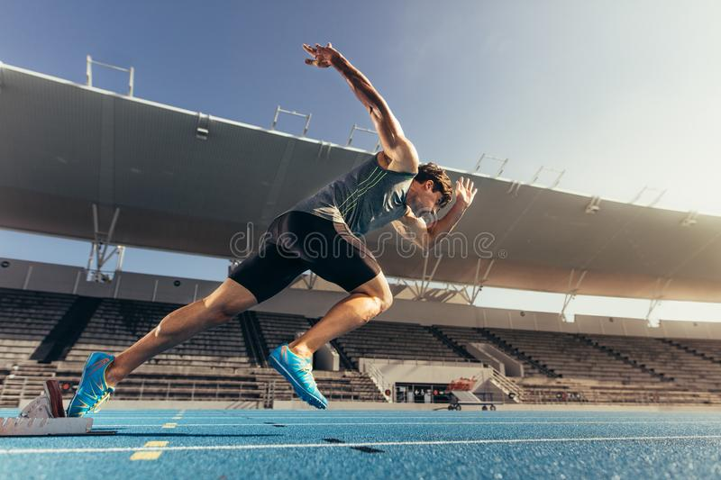 Sprinter taking off from starting block on running track stock images