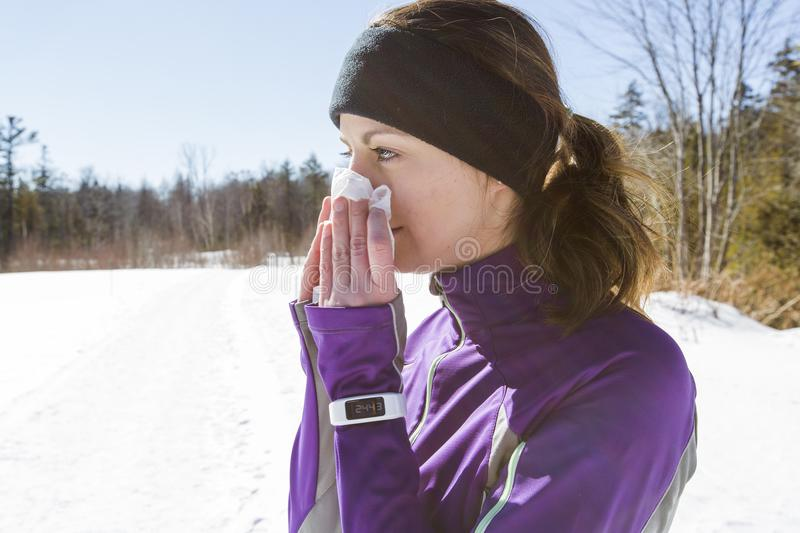 Runner Woman blowing her nose outside in the cold. A Woman blowing her nose outside in the cold royalty free stock photo