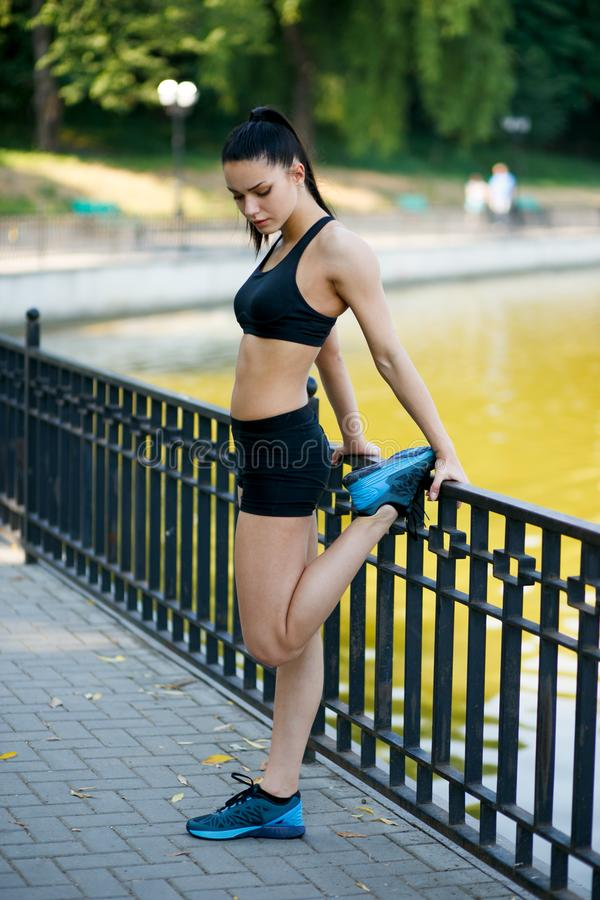 Beautiful fit female fitness girl model doing stretch exercising after workout outside by the lake in the summer time. royalty free stock photography
