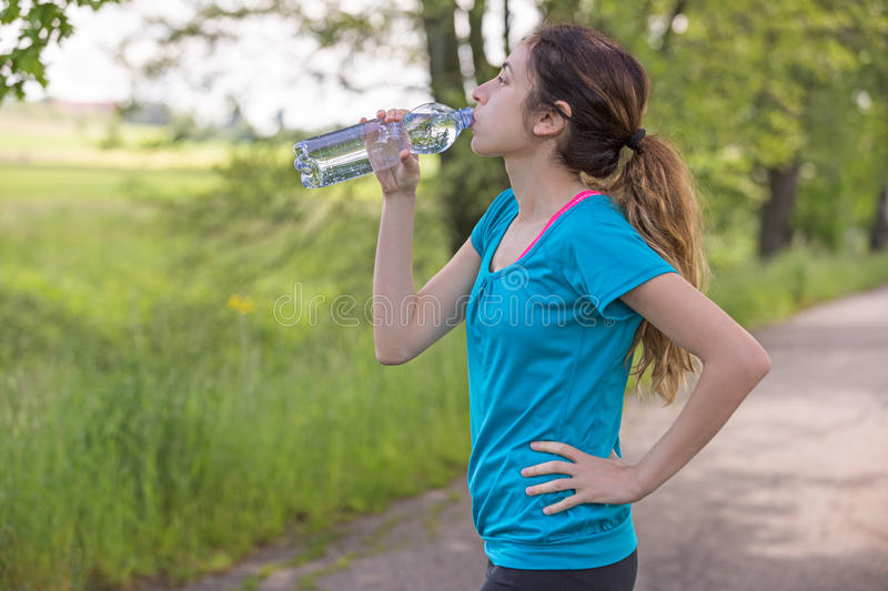 Runner woman drinking water royalty free stock images