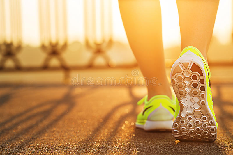 Runner woman feet running on road closeup on shoe. Female fitness model sunrise jog workout. Sports lifestyle concept. stock photo