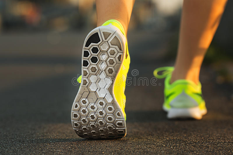 Runner woman feet running on road closeup on shoe. Female fitness model sunrise jog workout. Sports lifestyle concept. Runner woman feet running on road closeup stock photography