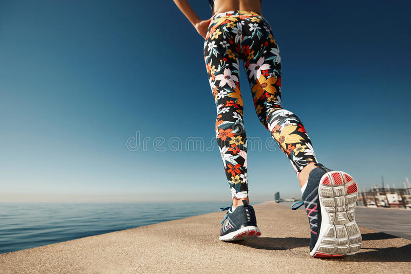 Runner woman feet running on road closeup on shoe. royalty free stock photography