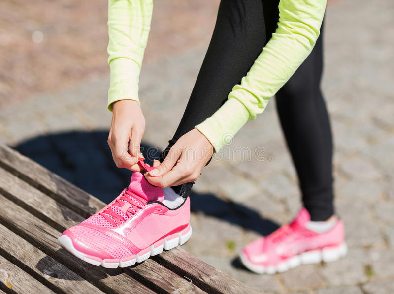 Runner woman lacing trainers shoes stock photos