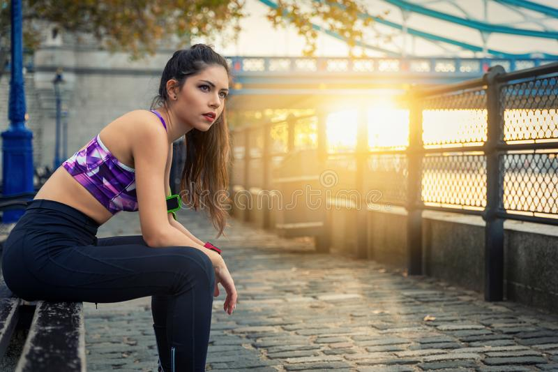 Runner woman resting after a early morning workout session. Athletic runner woman resting after a early morning workout session on sunrise in the city stock photography