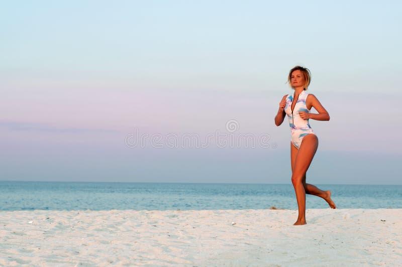 Runner woman running in the beach at sunset. stock photos