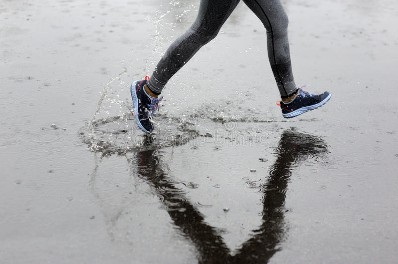 Runner woman running in Park in the rain. Jogging training for m royalty free stock image