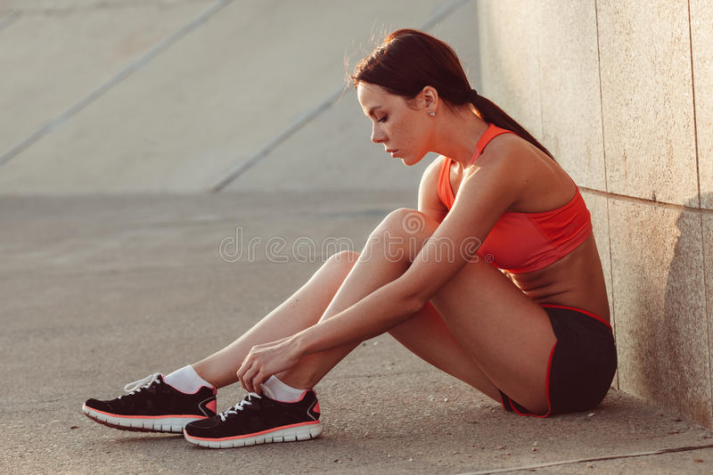 Runner woman sitting on the ground and tie laces royalty free stock images