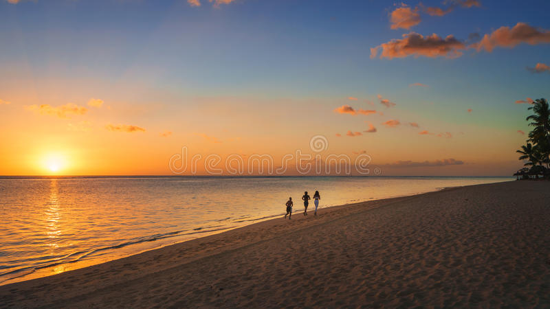 Runners on the beach at sunset stock photo