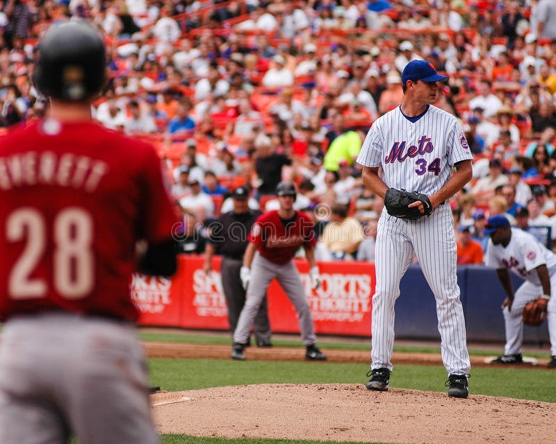 Runners on the corners. Mike Pelfrey. New York Mets pitcher Mike Pelfrey (34) pitches from the stretch with runners on first and third base in a game against the royalty free stock image