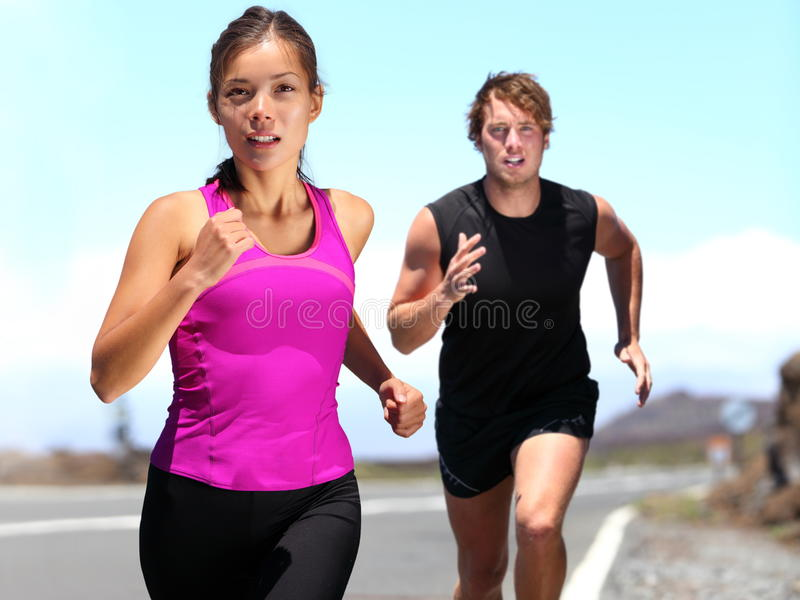 Runners - couple running. Training for marathon. Sport women and men jogging on road outside. Athletic female runner and male fitness model running at speed stock photo